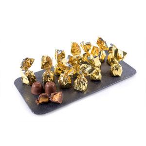 Bombón de Chocolate con Leche Relleno de Turrón Artesano de Jijona Marca Palmira Expuesto en Plato de Pizarra